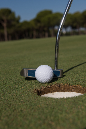 putter: close up of putter hitting golf ball to hole at course Stock Photo