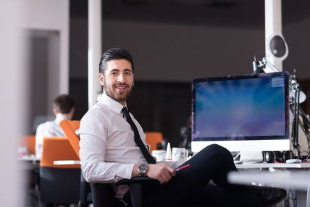 モダンな明るいスタートアップのオフィスのインテリアで自分の机にデスクトップ コンピューターで作業して幸せな若いビジネスマン