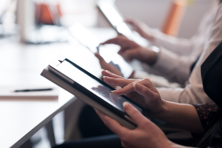 モダンな明るいスタートアップのオフィスのインテリアにタブレット コンピューターを使用してミーティングのビジネス人々 のグループ 写真素材