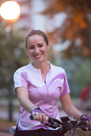 portrait of sporty happy woman with bike in park,  taking brake and relaxing after exercise photo
