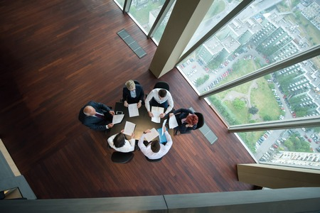 top view of happy  business people group on meeting throwing documents in air at modern office interior