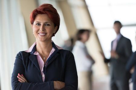 reunion de trabajo: pelirroja retrato de mujer de negocios de alto nivel corporativo de pie en el interior de la oficina FTON de su equipo como líder