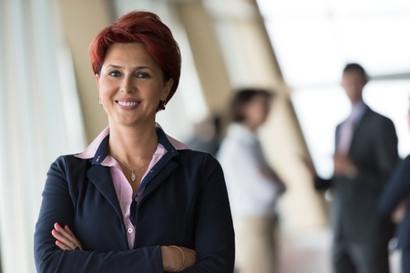redhair senior  business woman portrait at corporate office interior standing in fton of her team as leader