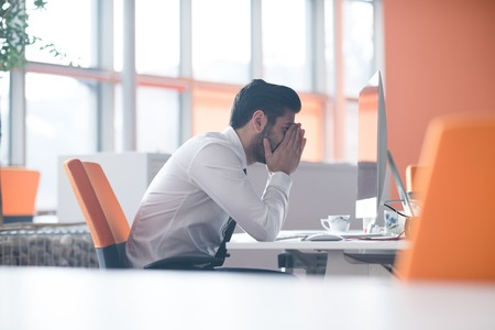 frustrierte junge Geschäftsmann auf dem Desktop-Computer zu modernen Startup-Büro-Interieur Arbeits