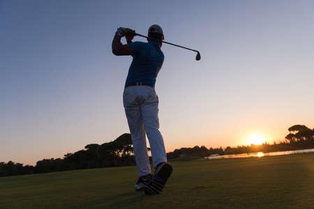 plan éloigné: golfeur hitting long shot avec chauffeur sur le cours au beau coucher de soleil