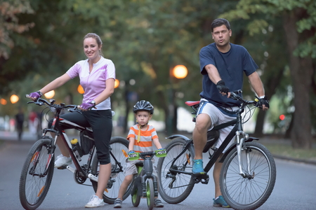 portrait of happy young family with bicycles in park at night photo