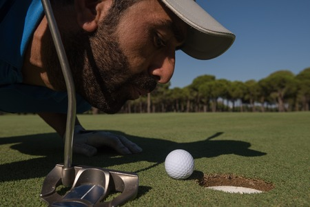 cheating: golf player blowing ball in hole. concept of cheating and success