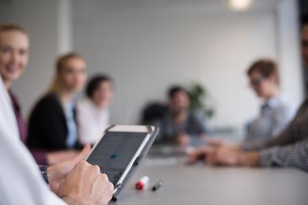 タブレット、用いたでぼやけてオフィス会議室で人々 のグループを使用して実業家の手のクローズ アップ