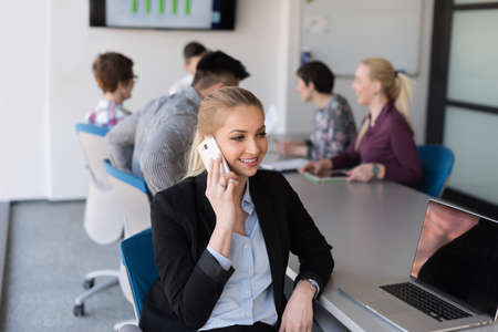 group meeting: young business woman speaking on phone at modern startup office interior, team in meeting group in background