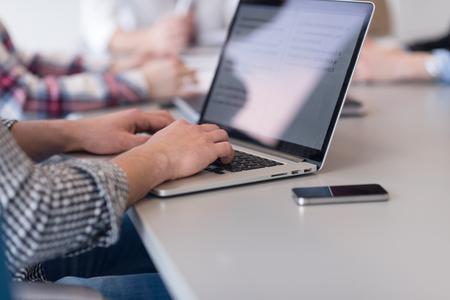 typing: primer plano de las manos del hombre de negocios que pulsa en el ordenador portátil en la oficina moderna puesta en marcha, el equipo desenfocada en el encuentro, el grupo de personas en el fondo