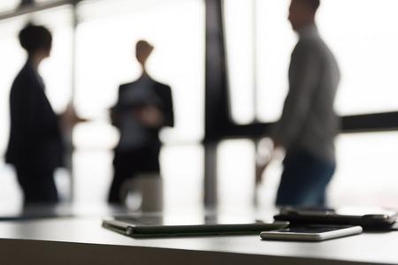 Gros plan de téléphone intelligent et ordinateur tablette au bureau salle de réunion. groupe gens d'affaires interagissant en arrière-plan.