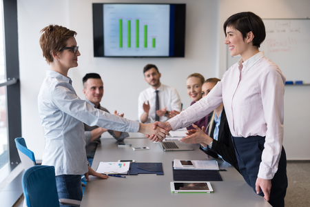group meeting: businesswomans handshake on team meeting  with group of people blured in background at modern startup business office interior