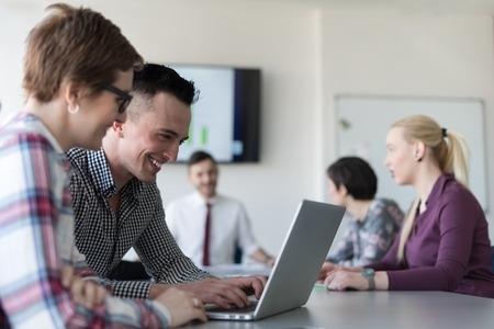 group of business people: young startup  business people, couple working on laptop computer,  businesspeople group on meeting in background at office interior Stock Photo