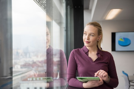 it: Blonde businesswoman in casual  clothes working on tablet computer at modern startup business office interior. Young people group on team meeting blured  in background Stock Photo