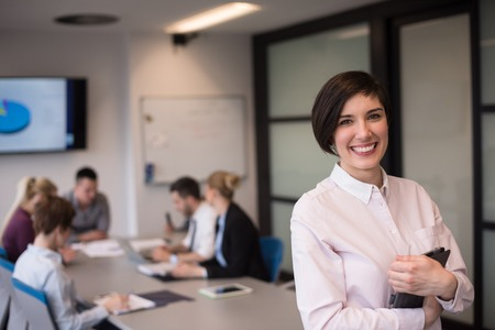 happy workers: young hispanic businesswoman portrait with  tablet computer at modern startup business office interior, people group on team meeting blured in background Stock Photo