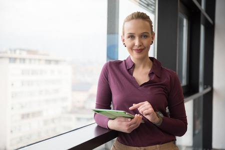casual office: Blonde businesswoman in casual  clothes working on tablet computer at modern startup business office interior. Young people group on team meeting blured  in background Stock Photo