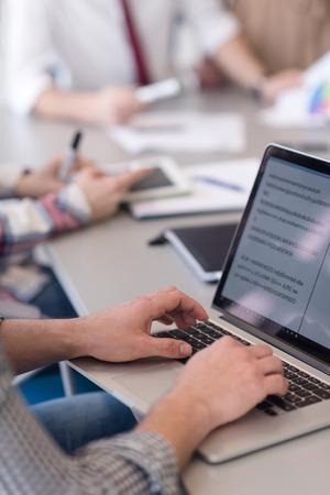 close-up van zakenman handen te typen op een laptop computer op moderne kantoor opstarten, blured team in vergadering, mensen groep op de achtergrond