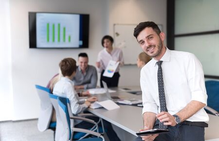 people office: Portrait of happy young businessman with tablet computer office. People group on team meeting in background