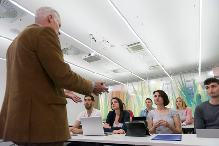 school classroom: group of students study with professor in modern school classroom