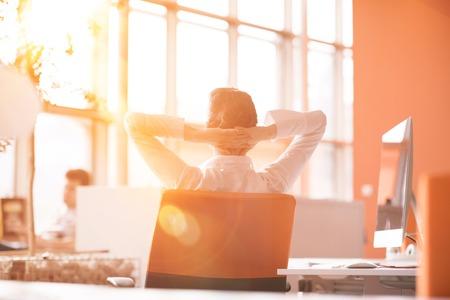 Felice giovane donna d'affari rilassante e ottenere l'ispirazione mentre si lavora sul computer desktop al moderno luminoso ufficio starup interni. Mattina alba o tramonto con sole splendere in background. Archivio Fotografico