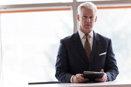 현대 밝은 사무실 인테리어에서 태블릿 컴퓨터에서 작동하는 회색 머리와 잘 생긴 수석 비즈니스 사람 스톡 콘텐츠 - 57006507