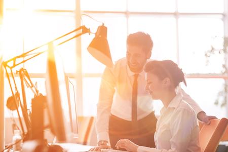 Business Paar zusammen auf Projekt im modernen Start Büro arbeiten. Am frühen Morgen Szene mit Sonne Flare im Hintergrund