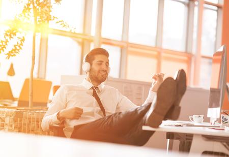 listening to music: Relajado joven empresario por primera vez en el lugar de trabajo en la mañana, escuchando música en los auriculares en la oficina moderna puesta en marcha. la flama del sol salida del sol en el fondo Foto de archivo