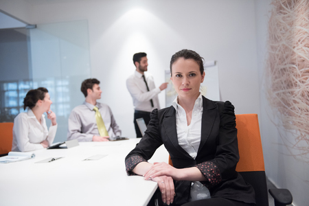 business woman: young business woman on meeting usineg laptop computer, blured group of people in background at  modern bright startup office interior taking notes on white flip board and brainstorming about plans and ideas