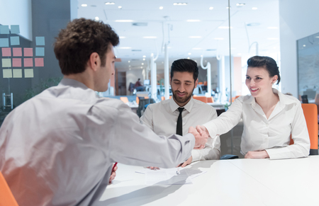 office life: signing contract on partners back, young couple on business meeting with life insurance and bank loan agent at modern office interior