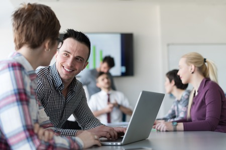start up: young startup  business people, couple working on laptop computer,  businesspeople group on meeting in background at office interior Stock Photo
