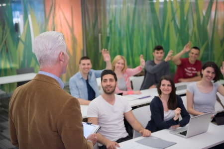 hands high: teacher teaching lessons, smart students group raise hands up in school  classroom
