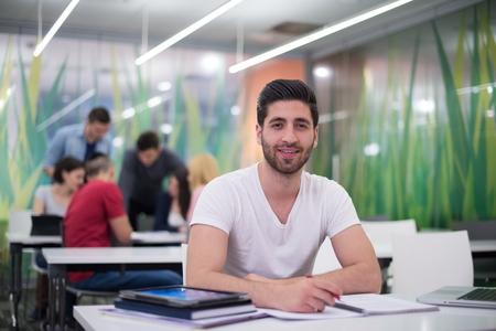 colegios: El estudiante masculino en el aula tareas de trabajo y aprendizaje con ordenador portátil, el grupo de estudiantes en el fondo