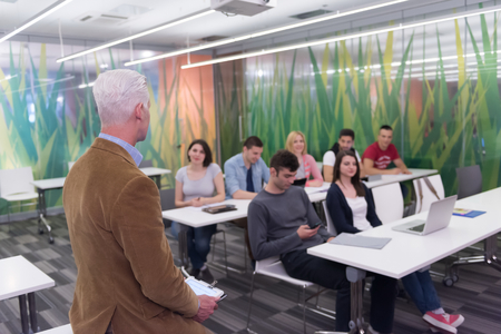 high class: group of students study with professor in modern school classroom