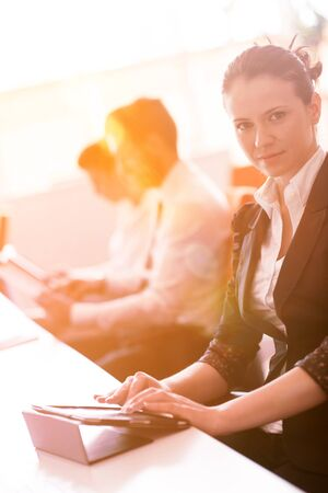 business team: business woman working on desktop computer at modern startup office, people group in background with sunrise or sunset and sun flare in background Stock Photo