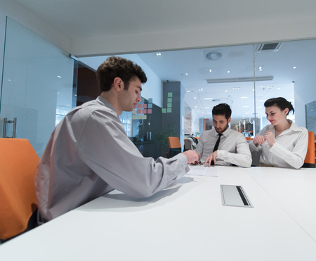 life partners: signing contract on partners back, young couple on business meeting with life insurance and bank loan agent at modern office interior