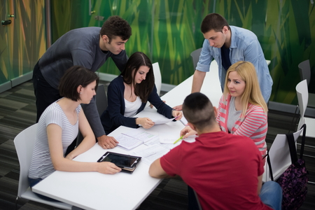 working on school project: students group study together in school classroom and working together homework project Stock Photo