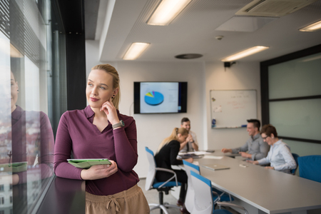 professional woman: Blonde businesswoman in casual  clothes working on tablet computer at modern startup business office interior. Young people group on team meeting blured  in background Stock Photo
