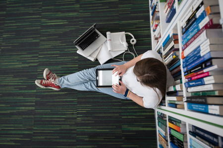 vrouwelijke student studeren in de bibliotheek met behulp van tablet en zoeken internet tijdens het luisteren van muziek en lessen op witte koptelefoon
