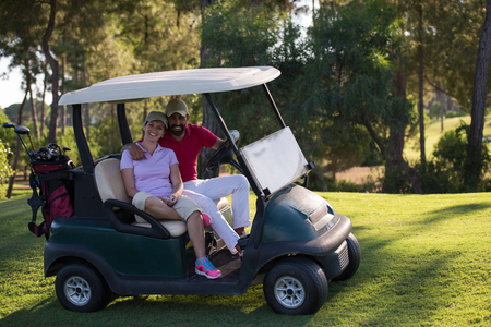 mid adult men: couple in buggy cart on golf course