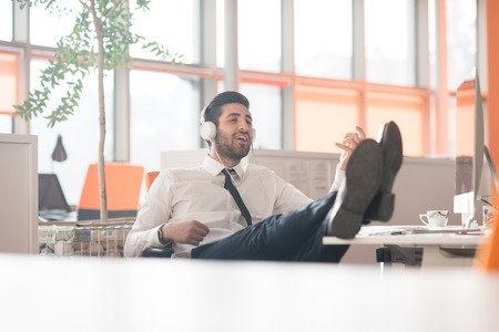 uomo felice: happy young arabian  business man with beard  listening music on headphones at modern startup office