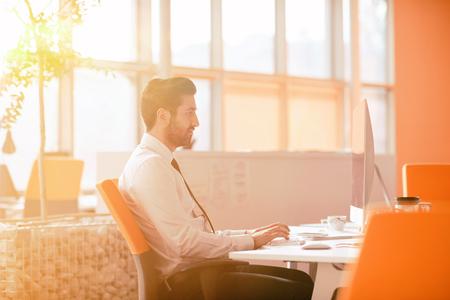 현대 사무실에서 헤드폰에 음악을 듣고, 이른 아침에 직장에서 첫 번째에 편안한 젊은 사업가. 백그라운드에서 일출 태양 플레어