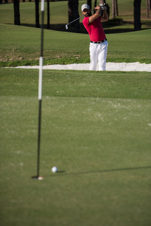 bunker: golf player shot ball from sand bunker at course