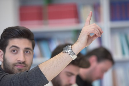 adult hand: group of  smart students raise hands up in school  classroom on class Stock Photo