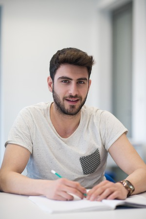 business education: male student taking notes in classroom. business education concept, casual young businessman on seminar training