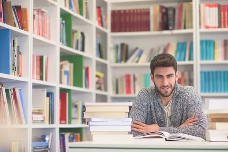 trabajando duro: Retrato de estudiante feliz mientras que la lectura de libros en la biblioteca de la escuela. lecciones de estudio para el examen. El trabajador duro y el concepto de persistencia.