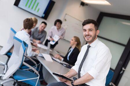 Portrait eines glücklichen jungen Geschäftsmann mit Tablet-Computer Büro. Menschen Gruppe auf Team-Meeting im Hintergrund