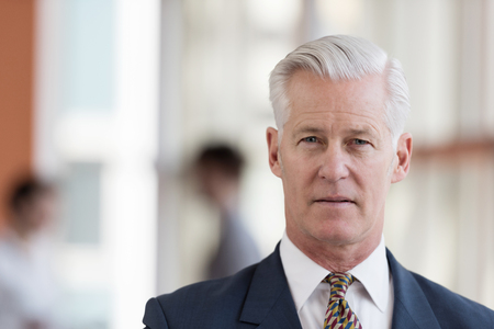 man hair: portrait of handsome senior business man with grey hait at modern bright office interior Stock Photo