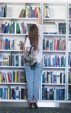 famale: smart looking famale student girl  in collage school library selecting book to read Stock Photo