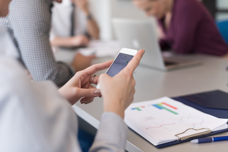 group of business people: close up of  businesswoman hands  using smart phone, people group in office meeting  room blurred in backgronud