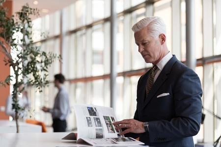 starszy człowiek biznesu czytania magazynu w nowoczesnym biurze jasny